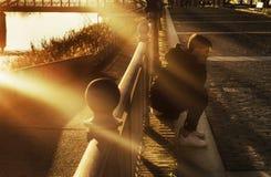 Garçon s'asseyant sur le plancher de ville au coucher du soleil avec des rayons de soleil image libre de droits