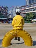 Garçon s'asseyant sur le pneu Images stock