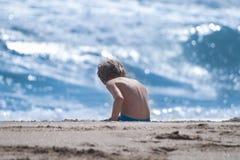 Garçon s'asseyant sur le sable à la plage Images libres de droits