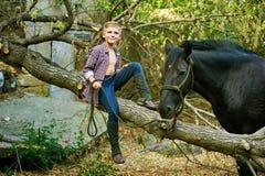 Garçon s'asseyant sur le vieil arbre posant avec un cheval après une séance d'entraînement Orientation sur le garçon Images stock