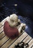 Garçon s'asseyant sur seule une passerelle Photo libre de droits
