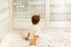 Garçon s'asseyant sur son lit et regardant la fenêtre Photo stock