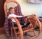 garçon s'asseyant sur une chaise de basculage Photos libres de droits