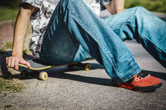 Garçon s'asseyant sur une planche à roulettes Photo libre de droits