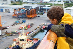 Garçon s'usant dans le regard de plaid au port Image libre de droits