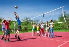 Garçon sautant pendant le match de volley sur la cour Photographie stock libre de droits