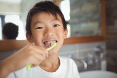 Garçon se brossant les dents dans la salle de bains Photographie stock libre de droits