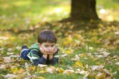 Garçon se situant en stationnement d'automne Photographie stock libre de droits
