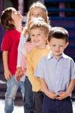 Garçon se tenant avec des amis dans une rangée au jardin d'enfants Photos stock