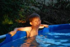 Garçon se tenant dans des rires de piscine Images stock