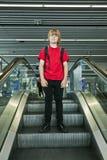 Garçon se tenant sur un escalator Photo stock
