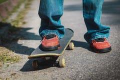 Garçon se tenant sur une planche à roulettes Photos libres de droits