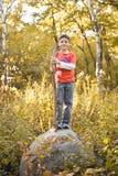 Garçon se tenant sur une roche photos stock