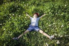 Garçon se trouvant sur l'herbe Photos libres de droits