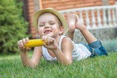 Garçon se trouvant sur l'herbe et manger l'épi de maïs dans le jardin images libres de droits