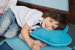 Garçon se trouvant sur l'oreiller en forme de coeur dedans Photographie stock libre de droits