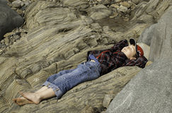 Garçon se trouvant sur la roche sur la plage Photographie stock
