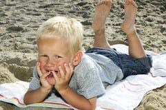 Garçon se trouvant sur une plage Image libre de droits