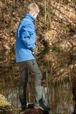 Garçon simple dans la veste bleue à l'étang seul pêchant Image stock
