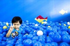 Garçon soulevant deux doigts dans la salle de jeux complètement des boules Photographie stock