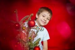 Garçon souriant par derrière un arbre de Noël avec les boules rouges Image libre de droits