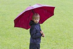 Garçon sous un parapluie sous la pluie outdoors images stock