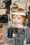 Garçon subissant l'essai d'examen d'oeil avec la lampe fendue photographie stock
