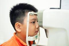 Garçon subissant l'examen d'oeil avec le microscope de lampe de fente Photo libre de droits