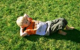 Garçon sur l'herbe verte photo stock