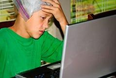 Garçon sur l'ordinateur portable chargé avec le mal de tête Image libre de droits
