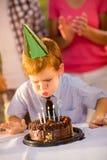 Garçon sur la fête d'anniversaire soufflant des bougies Photos libres de droits