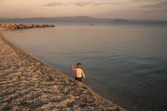 Garçon sur la plage Concept de solitude Main de ondulation d'enfant mignon au bord de la mer dans la soirée Le garçon s'assied en Photos stock