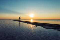 Garçon sur le chemin de fer au coucher du soleil de beauté photographie stock libre de droits