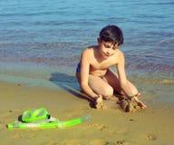 Garçon sur le jeu de se baigner de soleil de prise de plage avec le sable Photo stock
