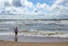 Garçon sur le rivage de la mer baltique agitée Image libre de droits