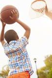 Garçon sur le tir de terrain de basket pour le panier Images stock