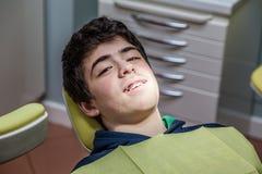 Garçon sur les accolades d'apparence de chaise de dentiste Images libres de droits