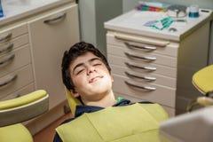 Garçon sur les accolades d'apparence de chaise de dentiste Photographie stock libre de droits