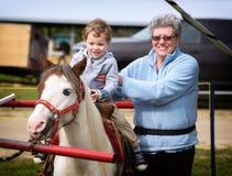 Garçon sur sa première Pony Ride avec sa grand-mère Photos stock
