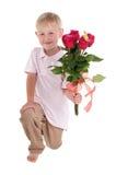 Garçon sur ses genoux avec des fleurs Image libre de droits