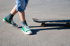 Garçon sur ses pieds et raie sur le trottoir. Photo stock