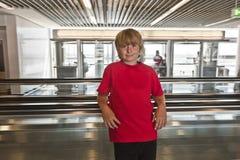 Garçon sur un escalier mobile à l'intérieur Images libres de droits