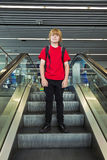 Garçon sur un escalier mobile Photographie stock