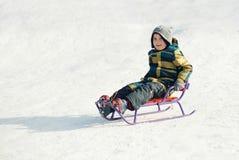 Garçon sur un traîneau dans la neige Photo stock