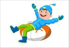 Garçon sur un traîneau pendant l'hiver Photo stock