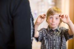 Garçon tenant des lunettes avec la mère dans le premier plan photo stock