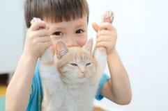 Garçon tenant des pattes antérieures de chat paresseux de gingembre Image libre de droits