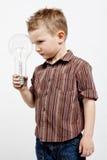 Garçon tenant l'ampoule énorme Photos libres de droits