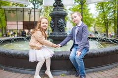 garçon tenant la main du ` s de fille Enfants s'asseyant à la fontaine extérieure Concept d'amusement d'amitié d'amour Petits adu Images stock