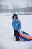 Garçon tenant la tuyauterie, se tenant sur la neige Image stock